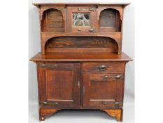 An arts & crafts stained oak dresser with leaded g