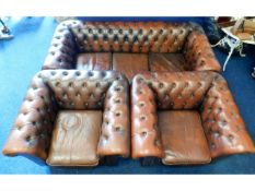 A brown leather Chesterfield style three piece sui