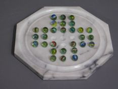 A marble solitaire board, three marbles missing