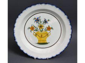 An 18thC. tin glaze delft plate with floral decor,
