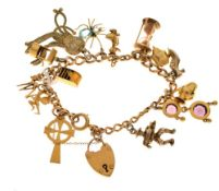 Yellow metal curb link charm bracelet with 9ct gold padlock and fifteen assorted charms, 39.8g gross