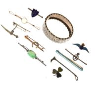 Assorted brooches to include RAF enamel, carved jade, moonstone, riding crop, miniature dagger