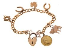 18ct gold curb link bracelet set with assorted gold and yellow metal charms and a plated padlock,