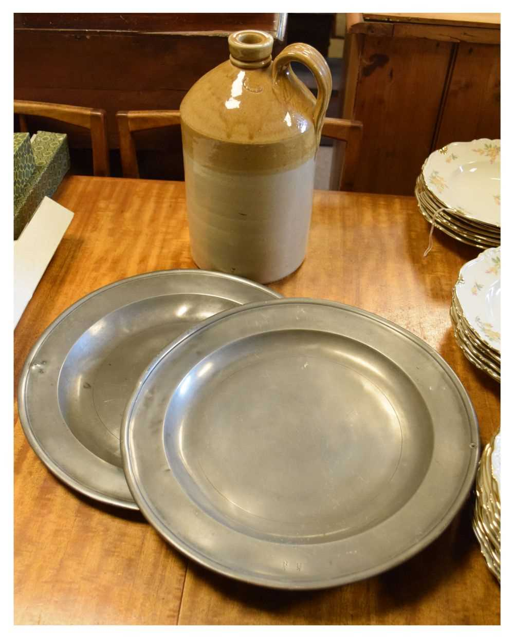 Pair of antique pewter plates, and a stoneware flagon