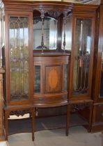 Edwardian mahogany bow front ornate display case with glassed doors and mirror back, standing on