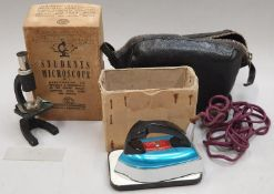 A vintage boxed Students Microscope together with a vintage boxed miniature travel Iron in leather