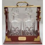 A pair of crystal cut glass decanters in tantalus with key.