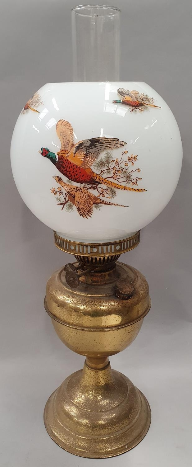 Brass oil lamp with flue and pheasant globe.