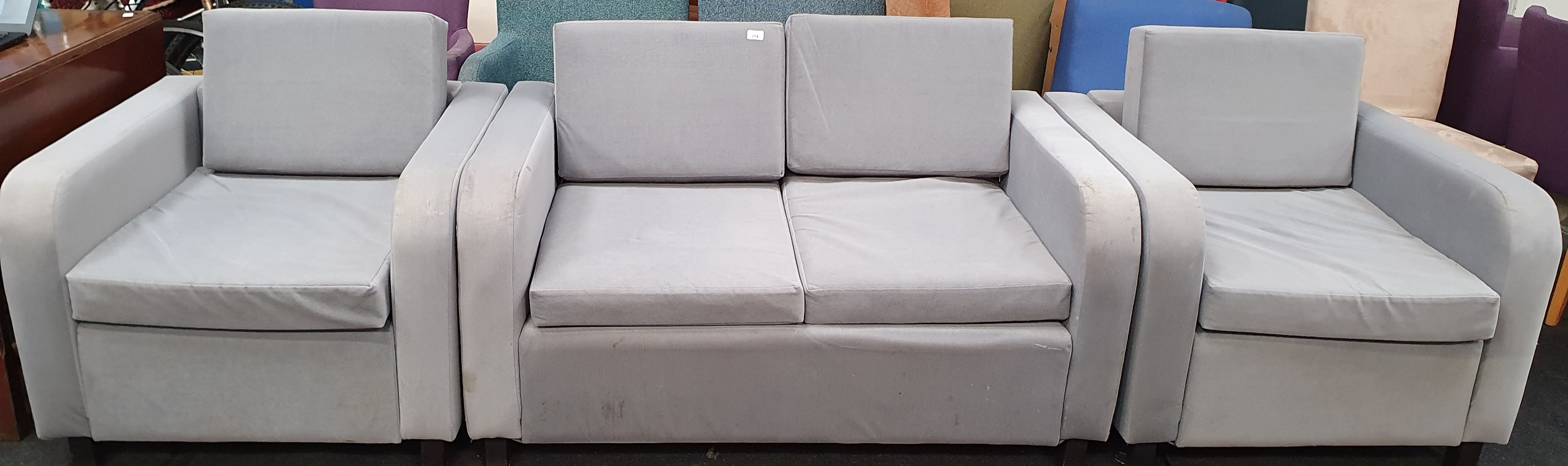 From a hotel clearance: Two armchairs and a two seater sofa in grey.