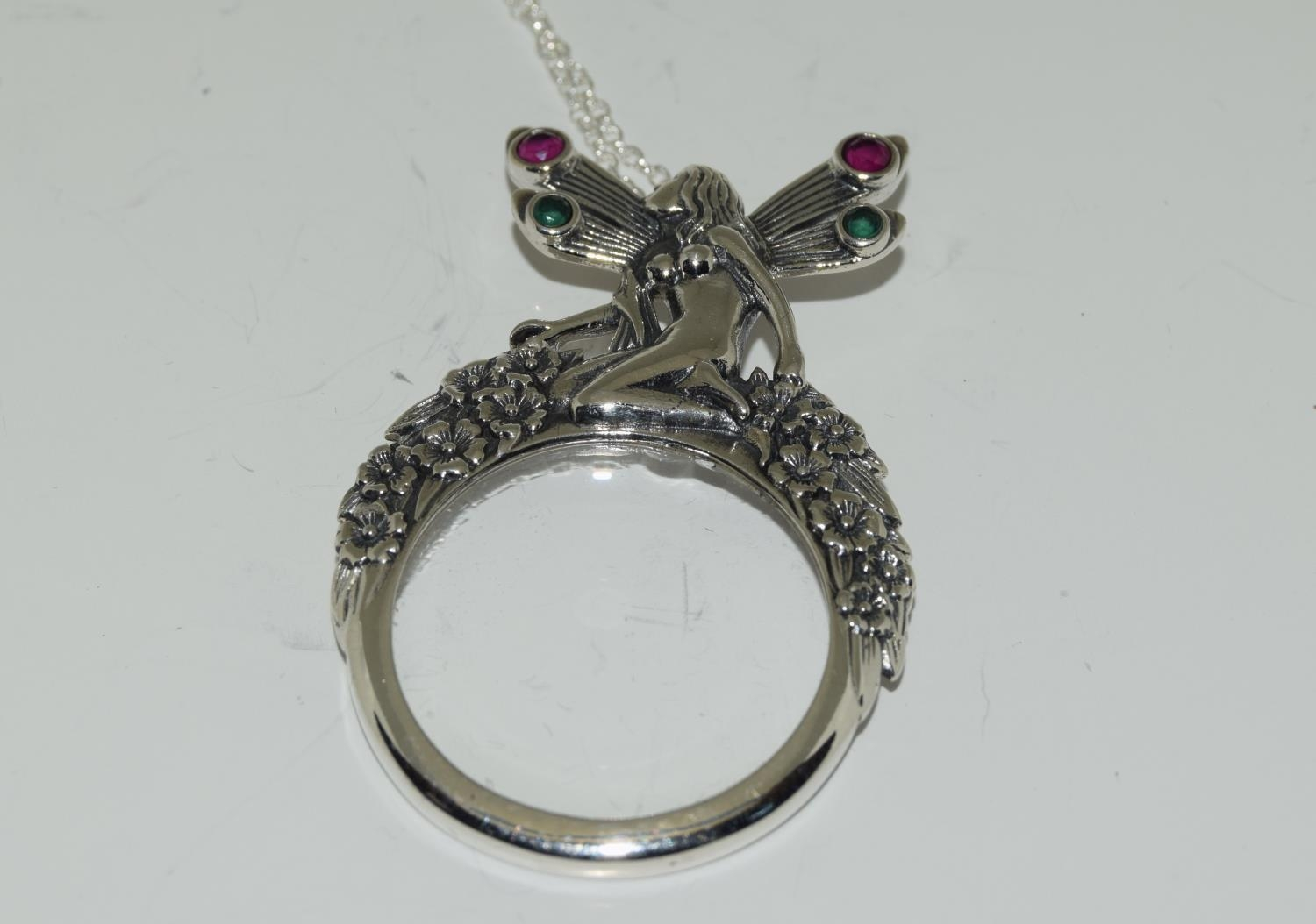 A silver magnifying glass pendant necklace with fairy finial set with Rubies.