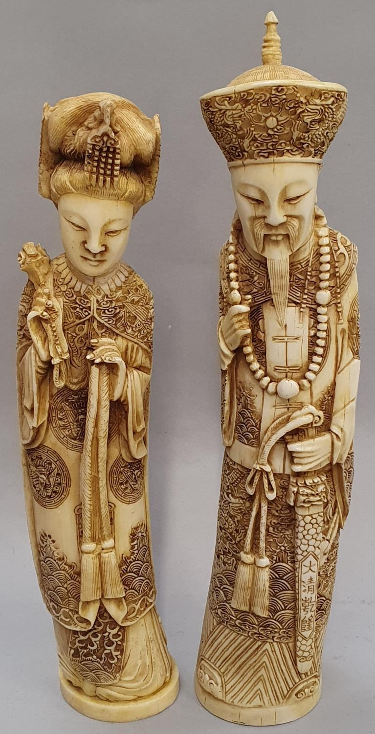 A pair of ivory coloured oriental figures 32 and 29cm high.