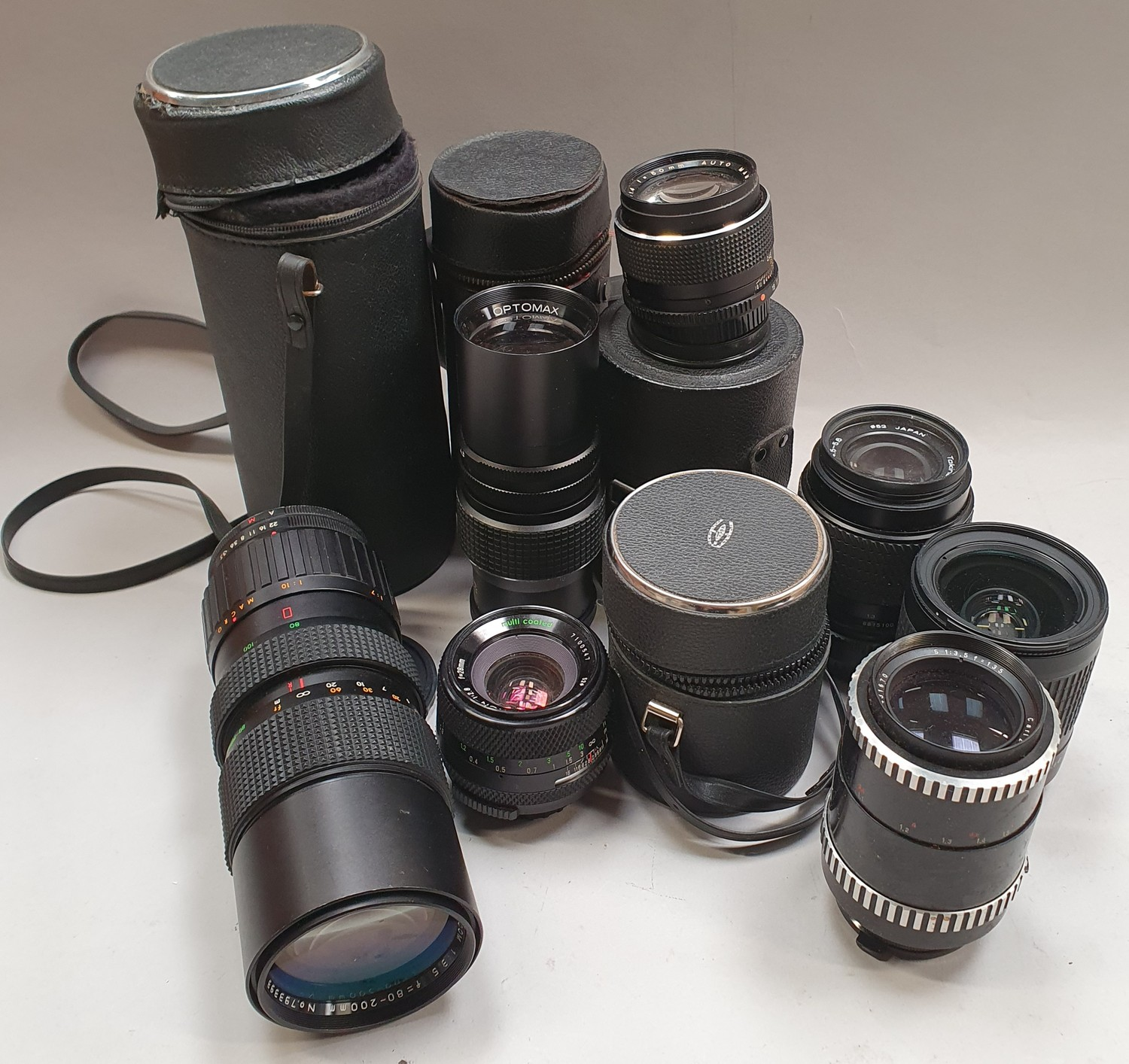 A collection of camera lenses to include Optomax, Nikon etc.