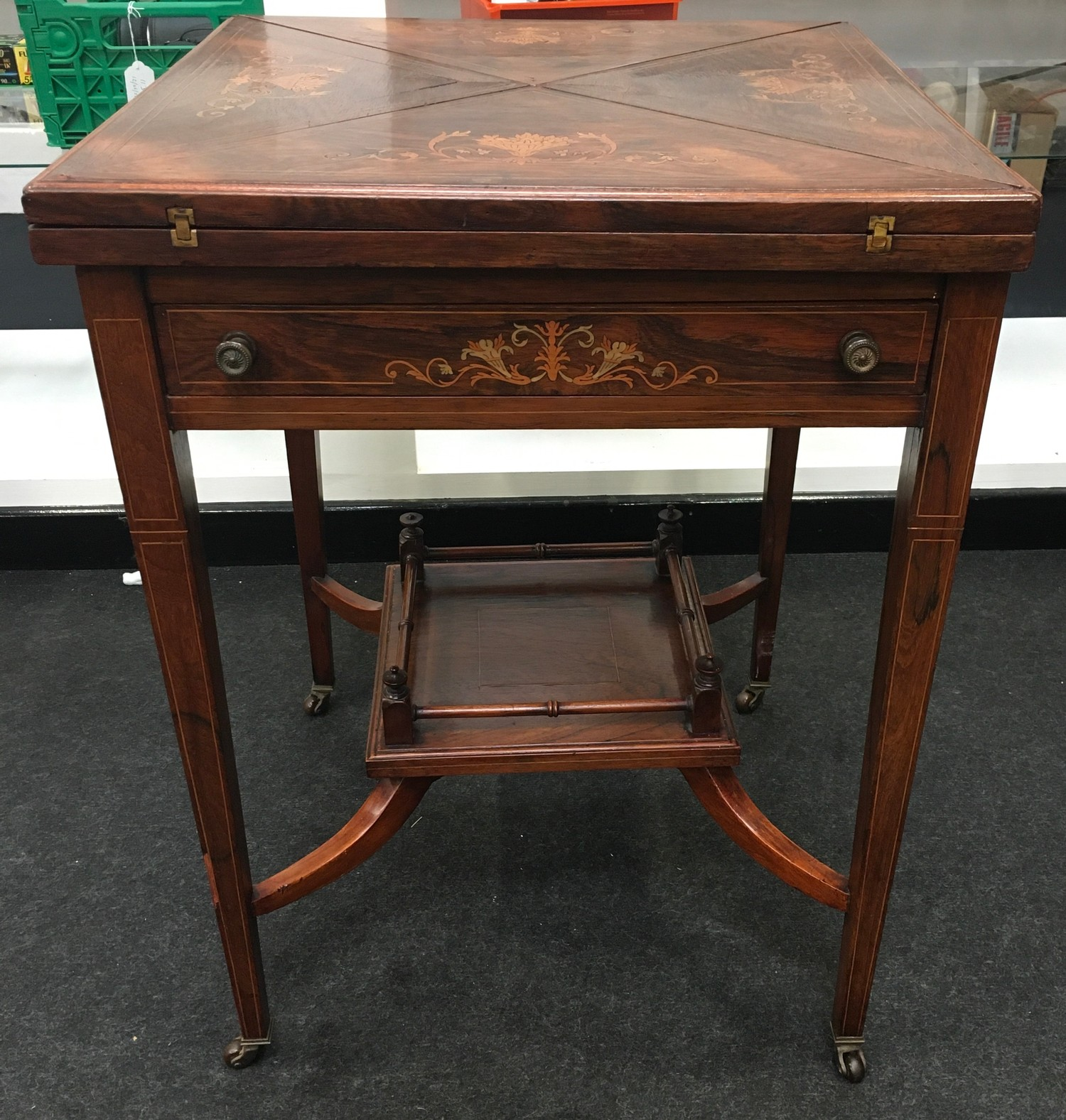 Edwardian inlaid rosewood envelope card table. The top decorated with urns and scrolled flowers,