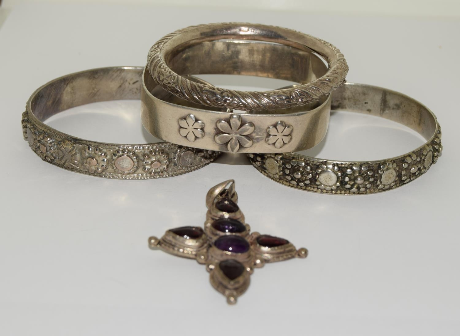 Four silver and white metal bangles together with a garnet and amethyst cross.