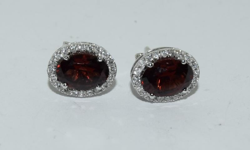 A pair of 18ct white gold garnet and diamond cluster earrings of 2.3cts Approx.