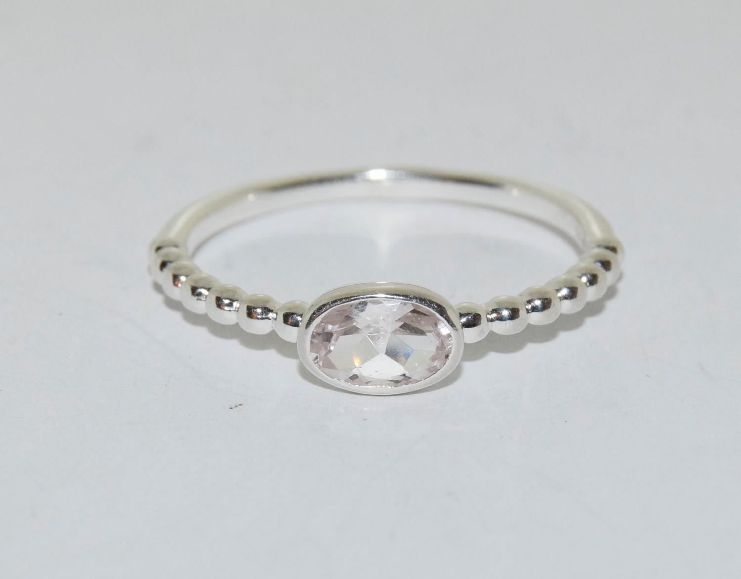 A silver ring with oval stone to centre, Size T 1/2.