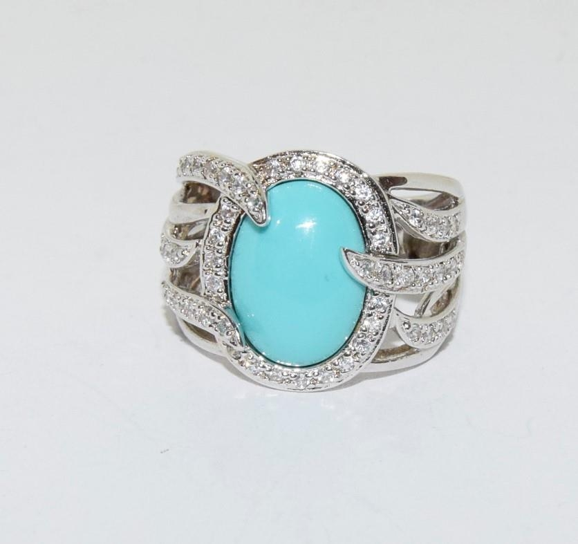 A silver ring with large turquoise stone to centre. Sixe Q