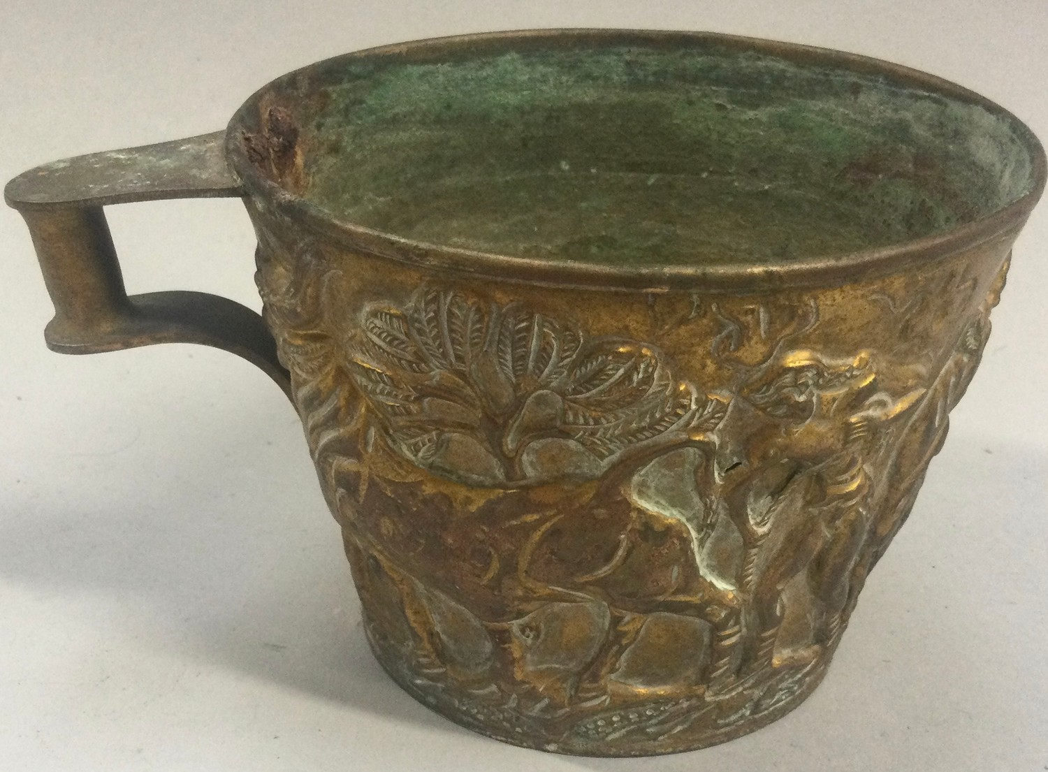 An Arts & Crafts brass Vapheio cup decorated with embossed figures.