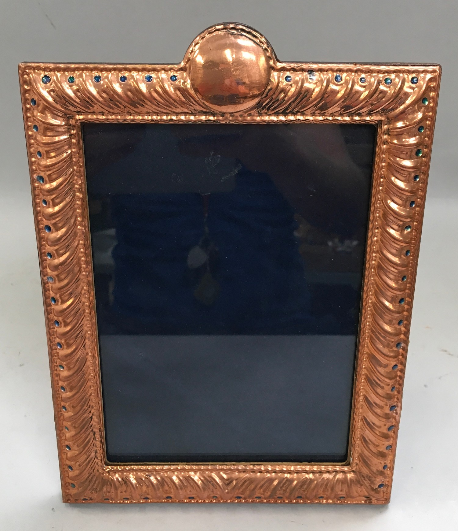 A Large copper and enamel easel back picture frame