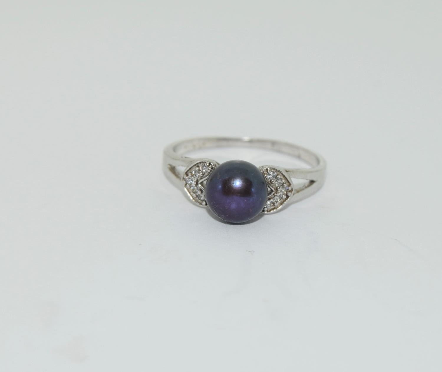 Silver ladies ring set with round pearl mount. Size O.
