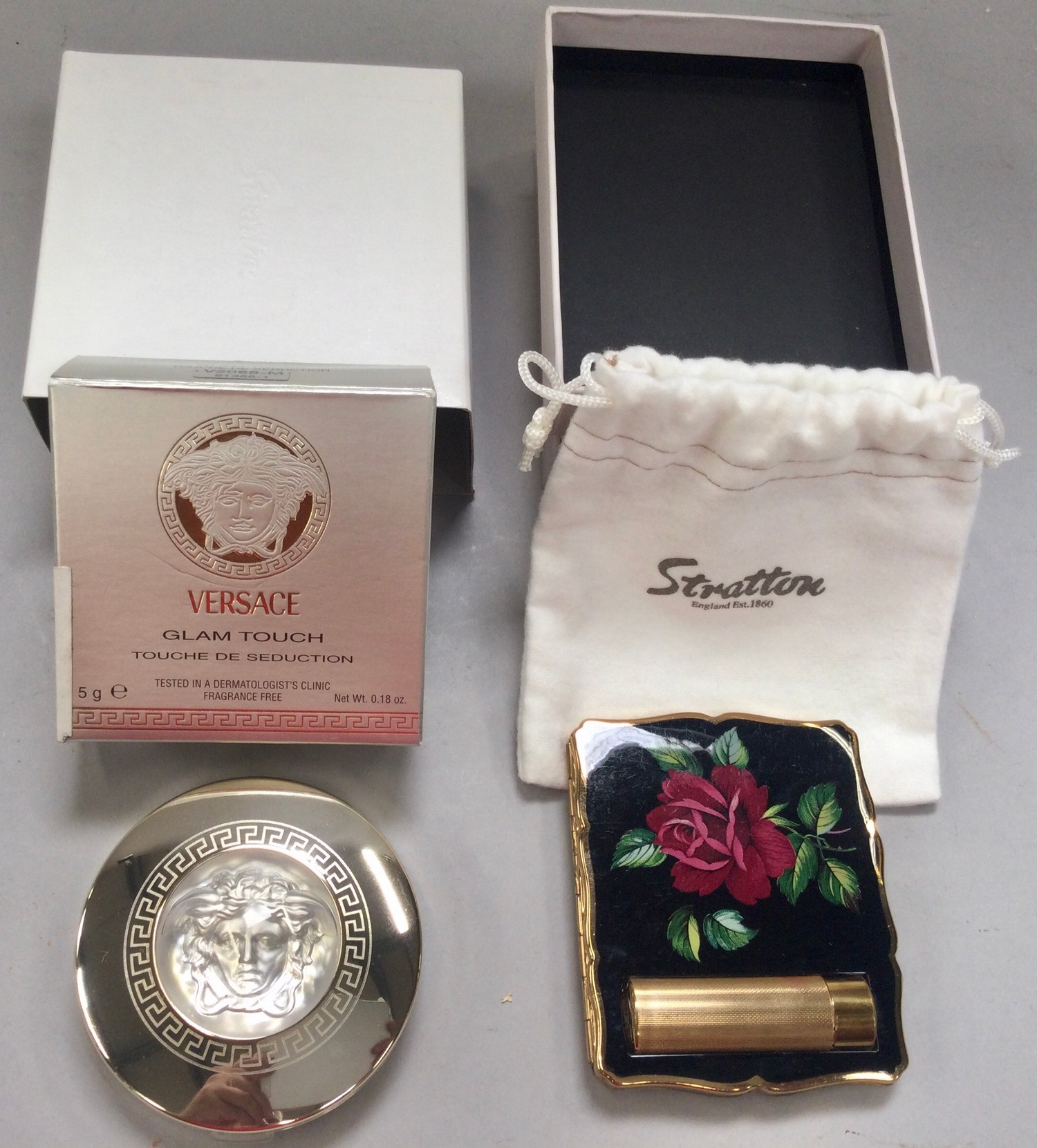 Stratton ladies compact with lipstick boxed with pouch together with Versace Glam Touch boxed