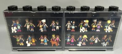 32 Lego Friends Minifigures with some animals and accessories in display cases.