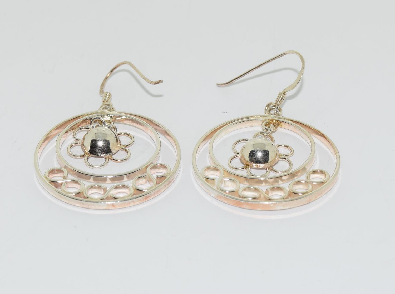 Ornate 925 silver daisy hoop earrings.