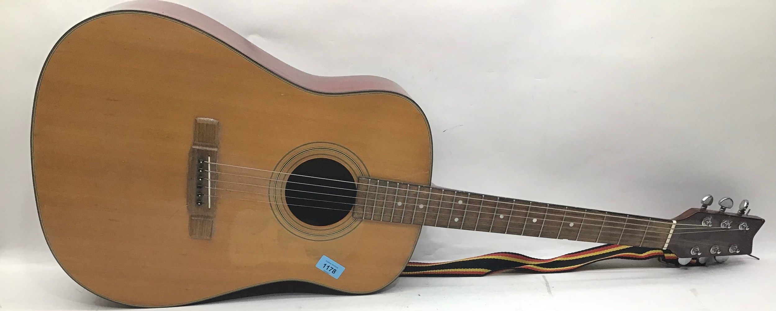 WASHBURN ACOUSTIC GUITAR. This 6 stringed guitar is finished in rosewood and comes with a strap.