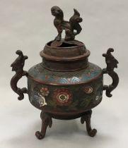 Oriental cloisonne incense burner with enamel decoration and dragon handles set on three legs