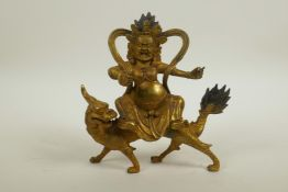 "A Sino-Tibetan gilt bronze of a wrathful deity riding a mythical beast, 8"" high"