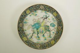 A Chinese famille verte enamelled porcelain cabinet dish decorated with a child riding a kylin, 6