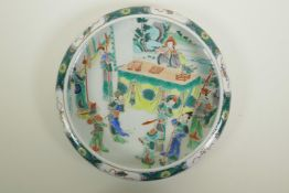 A Chinese famille verte porcelain dish with a rolled rim, decorated with figures in an interior