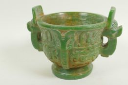 A Chinese carved green hardstone censer with two mask handles on pedestal base carved with birds and