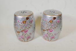 A pair of porcelain garden stools decorated with birds and flowers in bright enamels on a silver