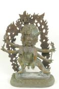 A bronze figure of a warlike Himalayan Buddhist deity, with three faces, six arms and four legs,