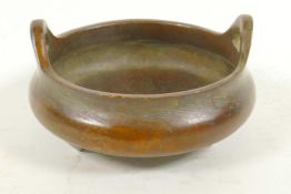 A Chinese bronze open censor with two loop handles raised on three feet, impressed seal mark to