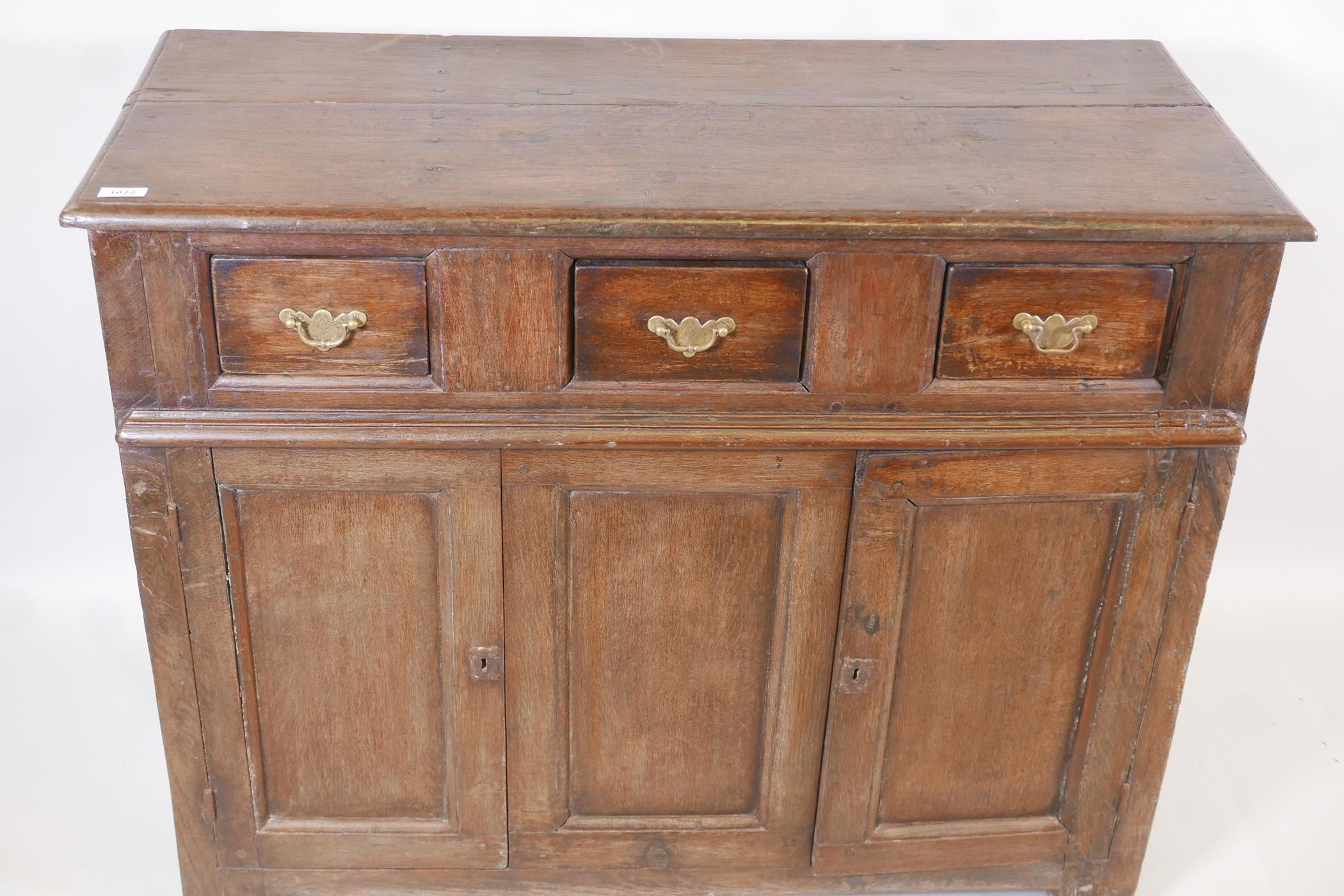 An antique oak side cabinet, with panelled ends and cupboards under three drawers, C18th and later - Image 3 of 5