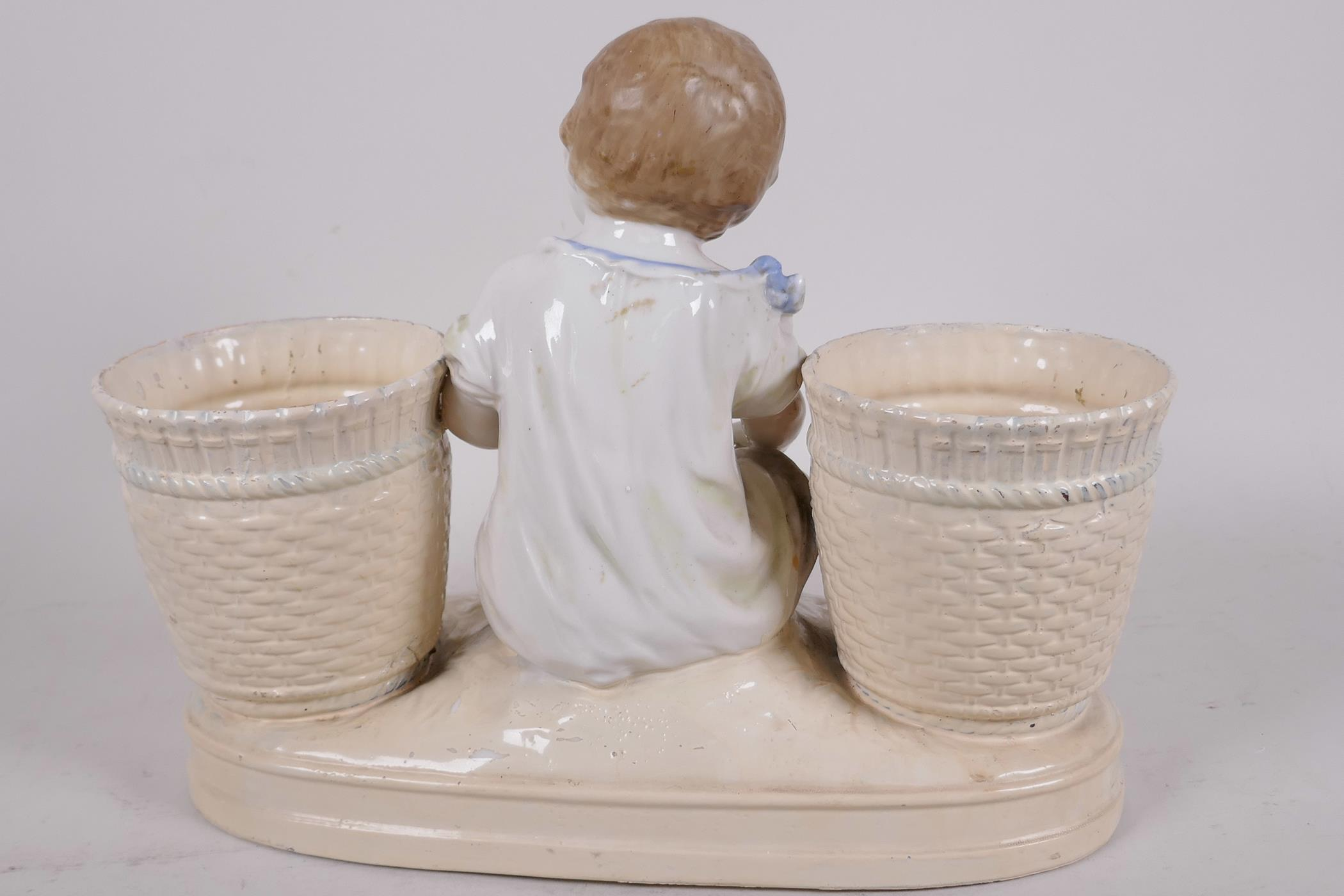 """A decorative porcelain planter in the form of a young girl seated between two large baskets, 11½"""" - Image 3 of 3"""