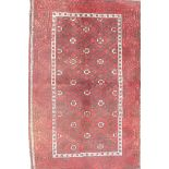 """A Middle Eastern red ground wool rug with a repeating diamond pattern design, 34"""" x 51"""""""
