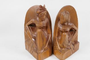 """A pair of Balinese hardwood bookends carved as male and female figures, 8"""" high"""