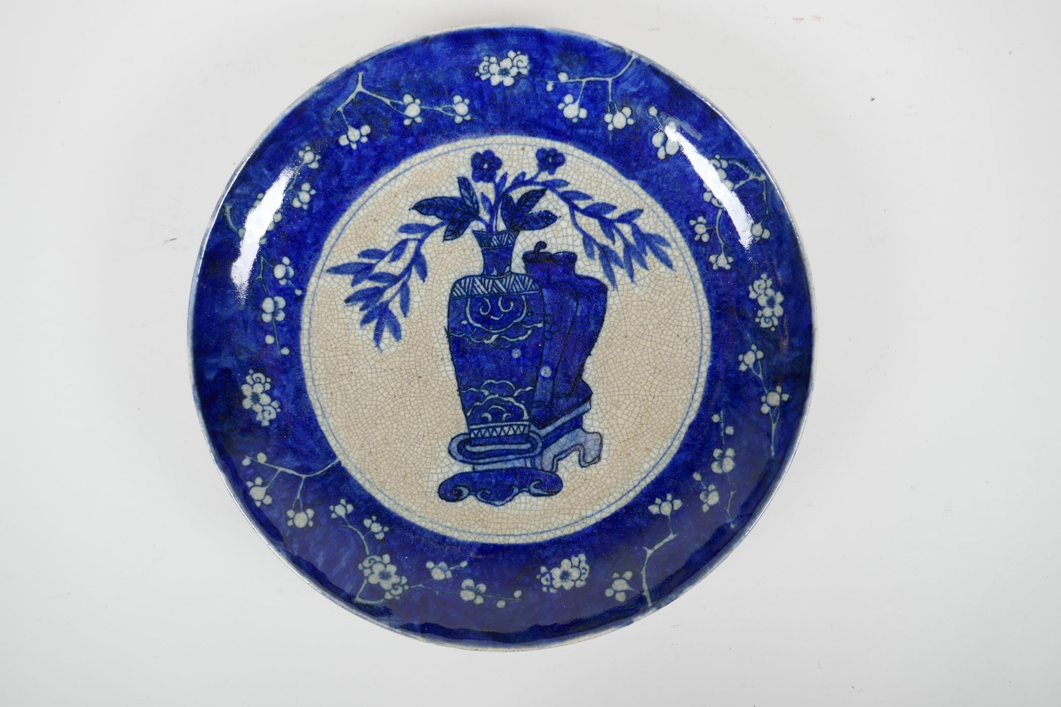 A Chinese early C20th blue and white crackleware charger decorated with objects of virtu within a