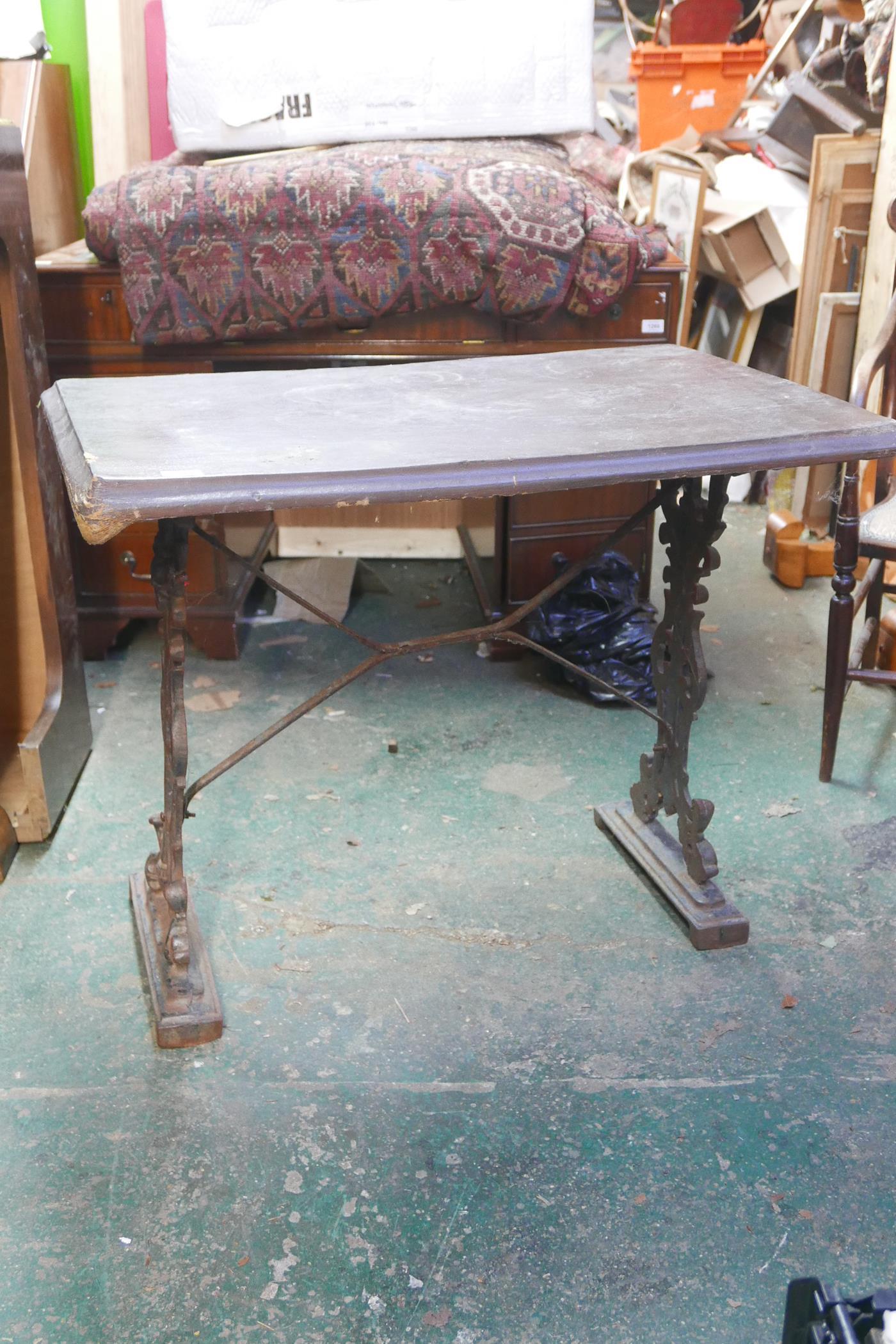 "A garden table with cast iron base, A/F, 28½"" high x 36"" x 24"""