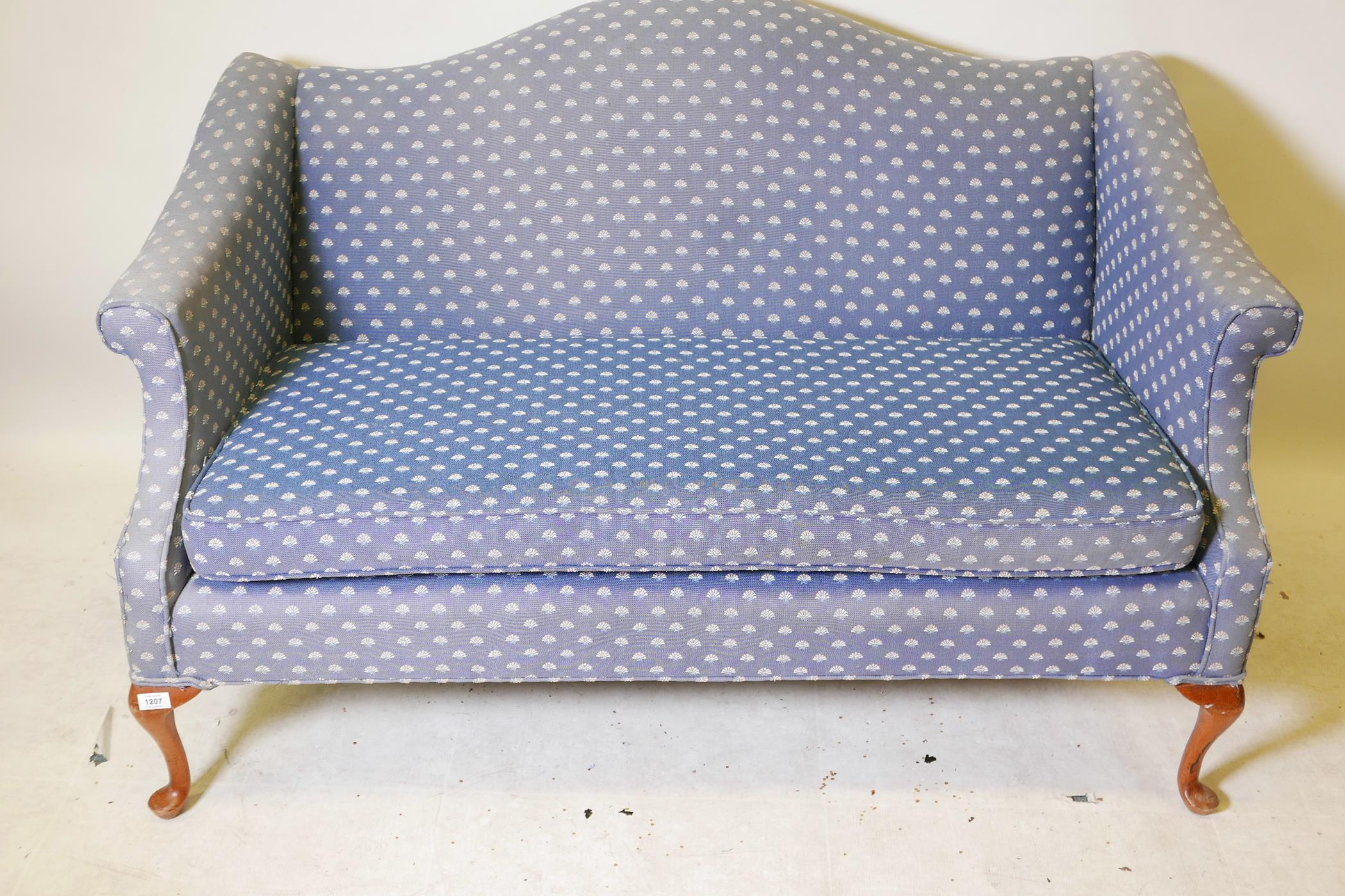 A Chippendale style two seater hump back settee with scroll arms, raised on cabriole supports with
