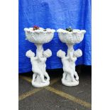 """A pair of painted concrete raised garden planters, the planters held aloft by two cherubs, 36"""" high,"""