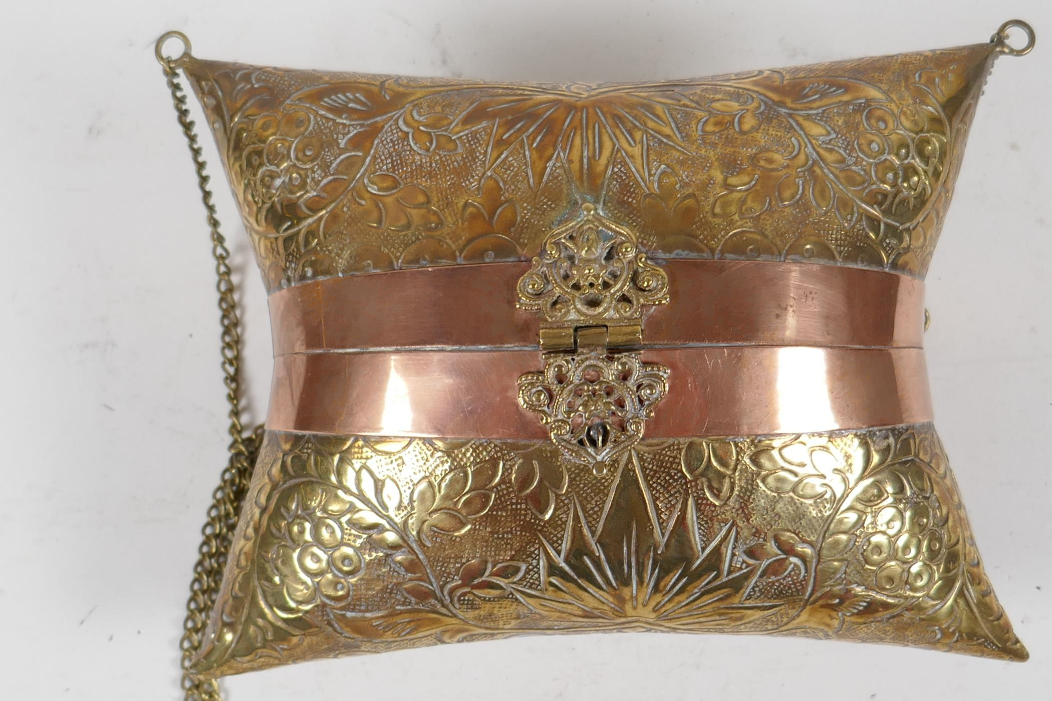 An Indian brass cushion shaped shoulder purse with engraved floral decoration, coppered bands and