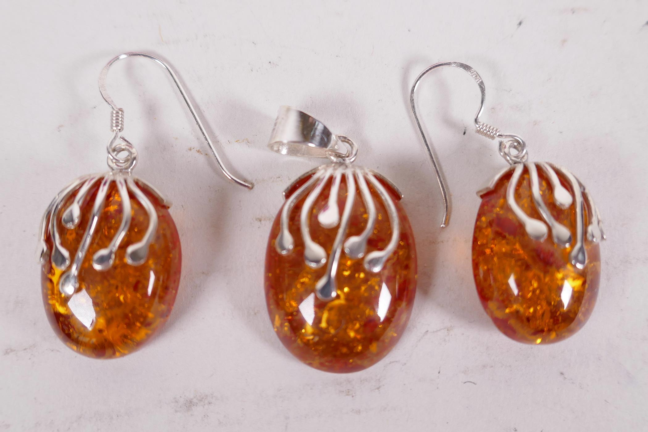 A silver and faux amber suite of earrings and pendant drop (3)