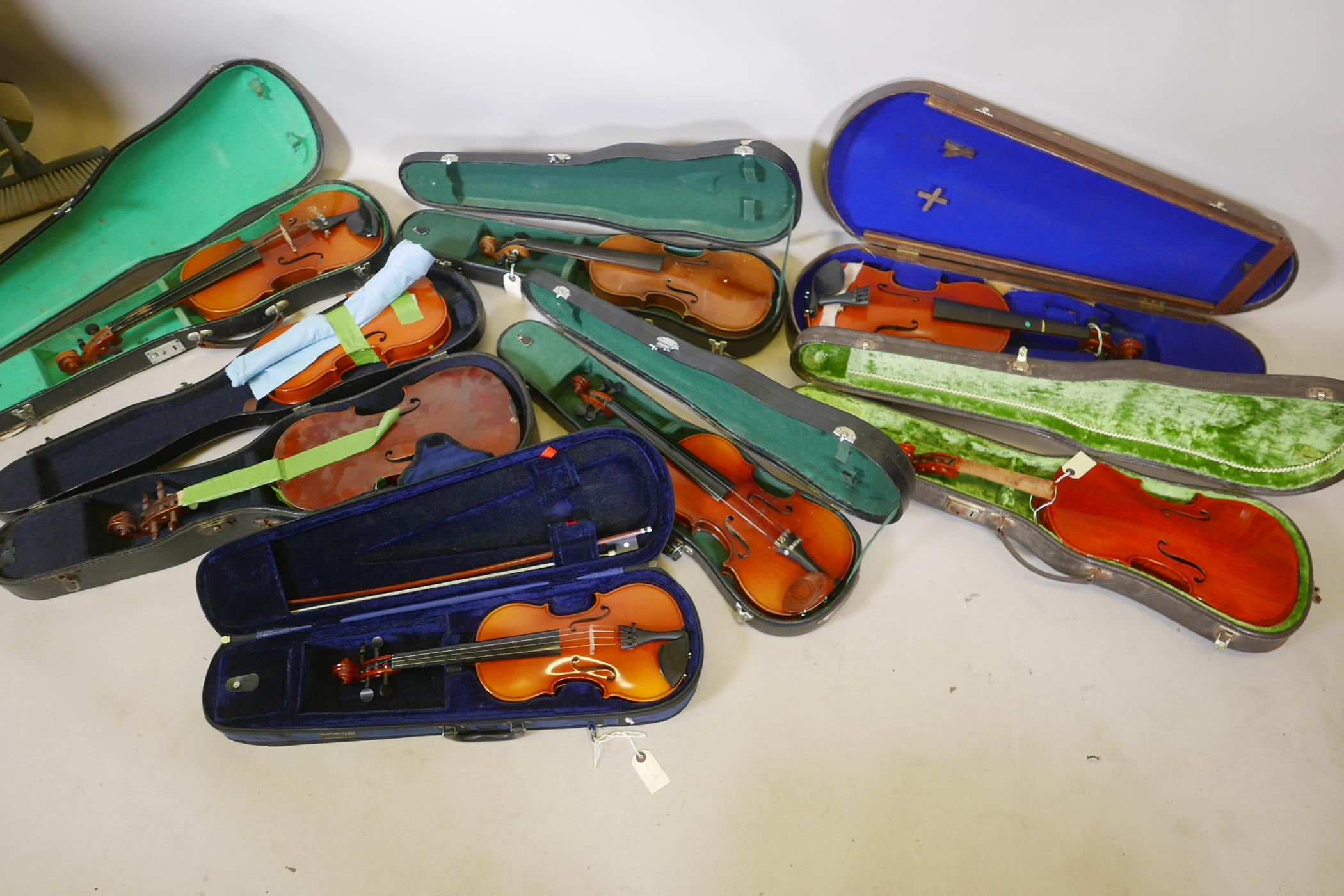 Eight violins for restoration, various states of disrepair, and including several good carry cases