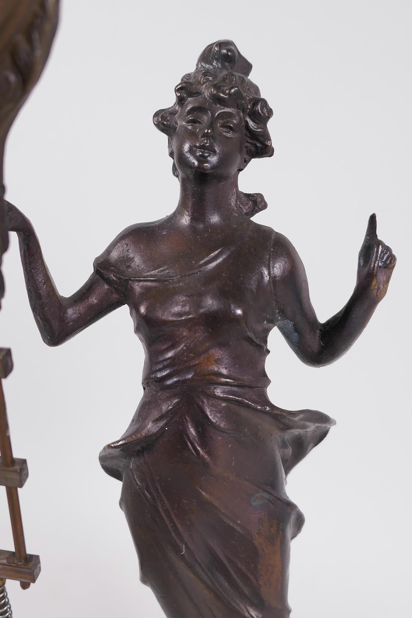 """A bronze mystery clock cast as an Art Nouveau style lady with the clock raised on one arm, 13"""" high - Image 2 of 4"""