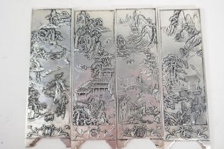 A set of four Chinese white metal scroll weights in the form of screen panels embossed with