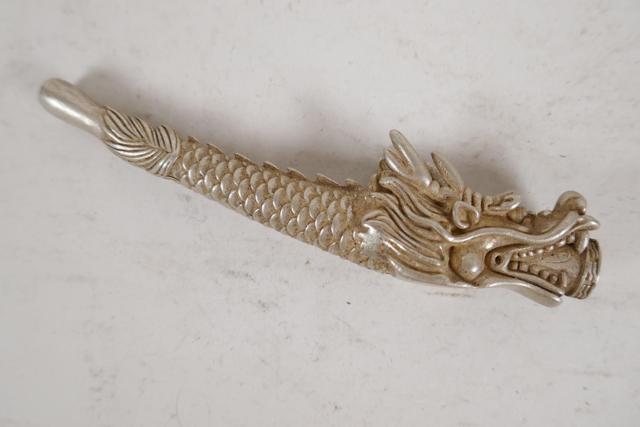"""A Chinese white metal cheroot holder cast in the form of a dragon, character mark to base, 4"""" long"""